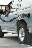 Автомобиль женщины дозаправляя на станции Стоковые Фото