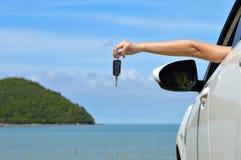 Автомобиль женщины счастливый показывая пользуется ключом вне окно Стоковое Изображение