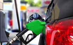 Автомобиль заправляя топливом нефть на станции стоковая фотография