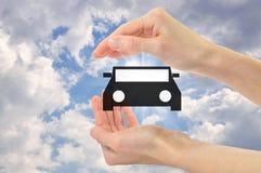 Автомобиль значка в руках против неба Стоковые Фотографии RF
