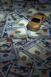 Автомобиль игрушки на куче долларов Стоковое Изображение