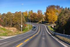 Автомобиль идет вниз с поворачивая сельского шоссе Стоковые Изображения RF
