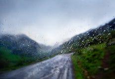 автомобиль и дорога в дожде через конспект окна отображают Стоковое Изображение