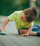 автомобиль мальчика меньшяя играя игрушка Стоковые Фотографии RF