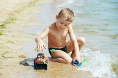 автомобиль мальчика меньшяя играя игрушка Стоковые Фото