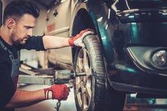 Автомобиль механика автомобиля изменяя катит внутри обслуживание ремонта автомобилей Стоковое фото RF