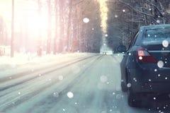 Автомобиль на заходе солнца зимы деревьев дороги Стоковое фото RF