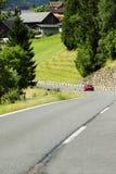 Автомобиль на дороге в горных вершинах Стоковые Изображения