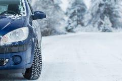 Автомобиль на дороге зимы с лесом в предпосылке Стоковое Изображение