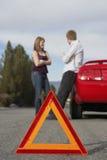 Автомобиль нервного расстройства пар готовя с предупреждающим треугольником в переднем плане Стоковое Изображение