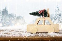 автомобиль нося рождественскую елку перед ландшафтом зимы Стоковые Фотографии RF