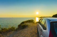 Автомобиль около океана на заходе солнца Стоковые Изображения RF
