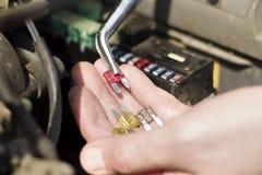 Автомобиль сплавляет на руке ` s механика Механик выбирает правильный взрыватель стоковые фотографии rf