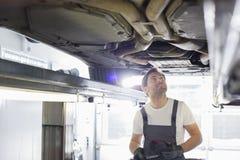 Автомобиль среднего работника механика автомобиля взрослого мужчины рассматривая в мастерской Стоковое фото RF