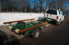Автомобиль с зеленым трейлером для того чтобы транспортировать шлюпку в месте для стоянки Стоковая Фотография RF