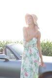 Автомобиль с откидным верхом счастливой женщины готовя против ясного неба Стоковые Фото