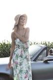Автомобиль с откидным верхом счастливой женщины готовя против ясного неба Стоковые Изображения RF