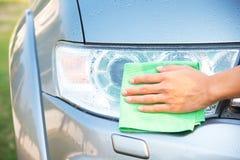 Автомобиль чистки с тканью microfiber полировать автомобиля фары Стоковая Фотография RF