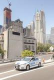 Автомобиль NYPD припарковал на улице с зданиями Манхаттана в расстоянии Стоковая Фотография