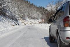 Автомобиль SUV на снеге покрыл дорогу горы Автошины автомобиля на дороге зимы покрытой с снегом Стоковые Изображения