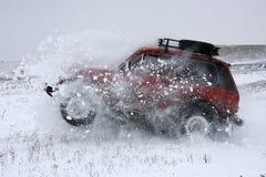 Автомобиль SUV ломает сугроб стоковое изображение