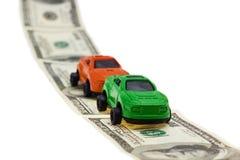 2 автомобиля игрушки на дороге денег на белой предпосылке Стоковые Фото