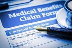 Авторучка, комод-часть стетоскопа и медицинская форма заявки преимуществ на доске сзажимом для бумаги Стоковое Фото