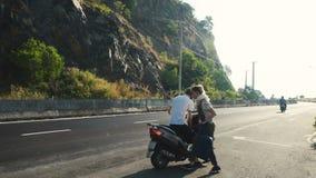 Автостопщик молодой женщины стоя на дороге видеоматериал