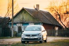 Автостоянка автомобиля Volkswagen Polo на проселочной дороге на предпосылке t Стоковое Изображение