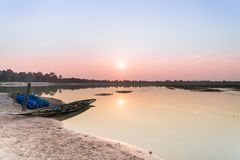 Автостоянка рыбацкой лодки на вечере берега реки заволакивает на заход солнца, Roi Et, Таиланд Стоковые Фото