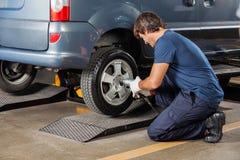 Автошина автомобиля отладки механика на ремонтной мастерской ремонта автомобилей Стоковые Фотографии RF