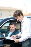Автодилер и молодой человек подписывая контракт Стоковые Изображения