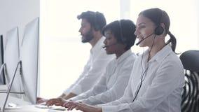 Агенты центра телефонного обслуживания советуя с клиентами на горячей линии на офисе видеоматериал