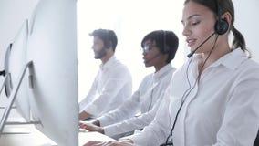 Агенты центра телефонного обслуживания советуя с клиентами на горячей линии на офисе сток-видео