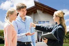 Агент недвижимости давая ключ дома молодым парам стоковая фотография rf