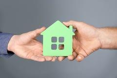 Агент недвижимости и старший человек держа дом моделируют Стоковое Изображение