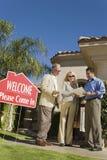 Агент недвижимости обсуждая контракт с парами Стоковое Фото