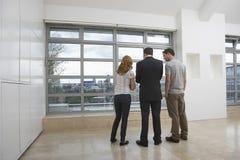 Агент недвижимости показывая парам новую квартиру стоковая фотография rf