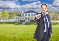 Агент недвижимости с ключами дома перед домом стоковые изображения rf