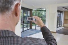 Агент недвижимости фотографируя новое свойство стоковое фото