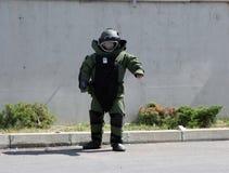 Агент обезвреживания неразорвавшихся бомб в костюме бомбы разоружает бомбу внутри автомобиля террористов в городе Софии, Болгарии Стоковая Фотография RF