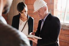 Агент по продажам показывая новый дом для того чтобы экономно расходовать и жена стоковая фотография