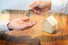 Агент по продаже недвижимости в костюме сидя в столе офиса вручая сверх h Стоковое фото RF