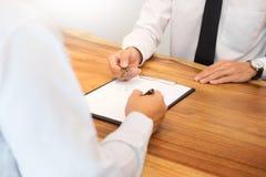 Агент по продаже недвижимости в костюме сидя в столе офиса вручая сверх h Стоковые Фото