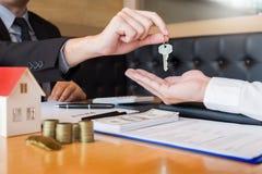Агент по продаже недвижимости давая дом пользуется ключом свойство согласования знака клиента для продажи, покупающ и продающ кон стоковые изображения