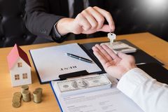 Агент по продаже недвижимости давая дом пользуется ключом свойство согласования знака клиента для продажи, покупающ и продающ кон стоковое фото