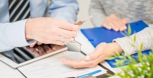 Агент по продаже недвижимости давая ключи дома к клиенту Стоковое Изображение