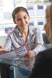 Агент по продаже недвижимости обсуждая свойство с клиентом в офисе Стоковое Изображение