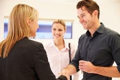 Агент по продаже недвижимости тряся руки с клиентами в пустом офисе Стоковые Фотографии RF