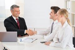 Агент по продаже недвижимости тряся руки с парами Стоковое Изображение